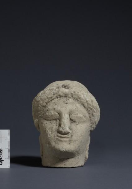Limestone female head of votive statuette with sakkos and rosette earrings, fragment of votive-statuette