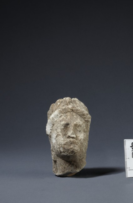 Limestone head of female votary with leaf-wreath and veil, fragment of votive statuette