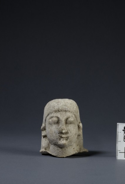 Limestone head of female votary with Egyptianising kerchief covering the hair, fragment of votive-statuette