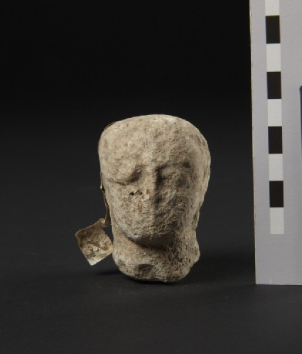 Limestone head of temple-boy with earring, fragment of votive-statuette