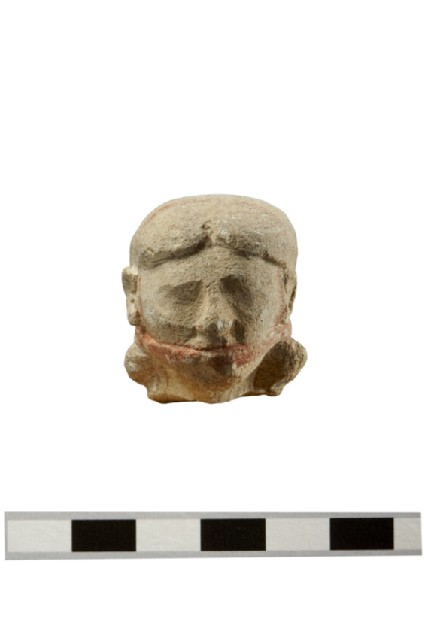 Head of a male double- flute player votive figure in limestone, Egyptianising