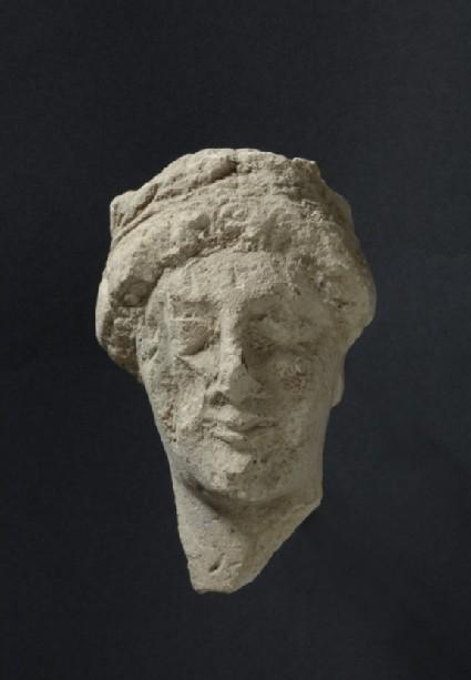 Limestone head of female votary with fillet, votive-statuette