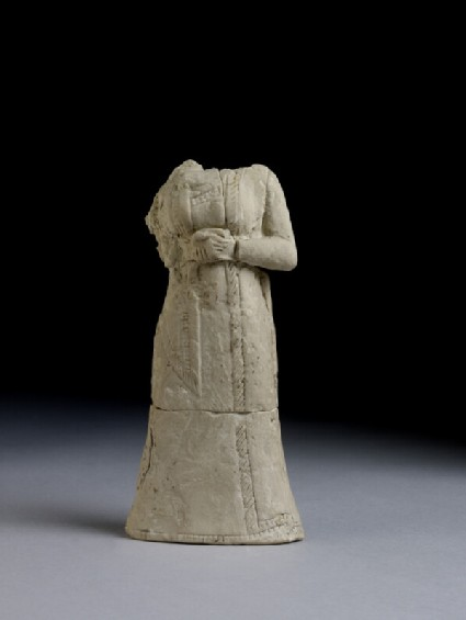 Statuette of a headless woman wearing a long robe and cloak
