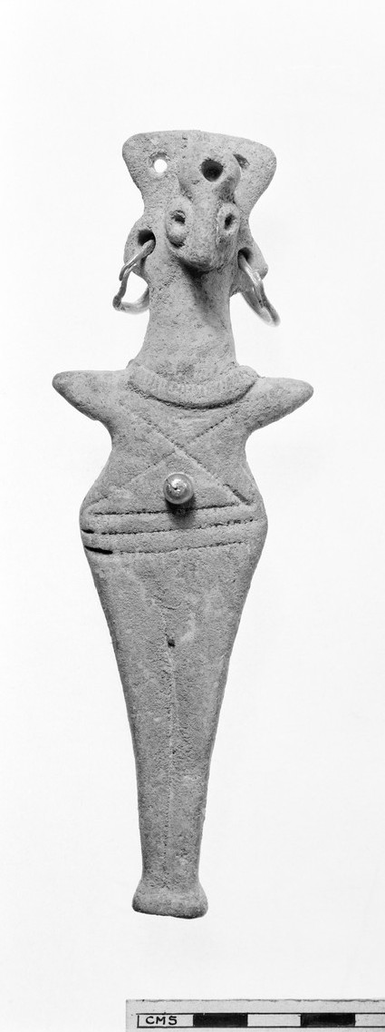 Figurine with bird-like head, flattened body, pointed arms, holes in body and head for gold decoration