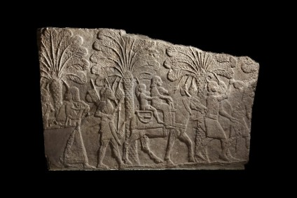 Relief depicting Babylonian campaign, woman and child captives riding on mule are escorted by Assyrian soldiers along the edge of a river, fragmentary