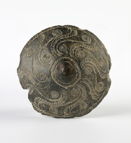 Stone sword pommel decorated with incised spirals and curved lines