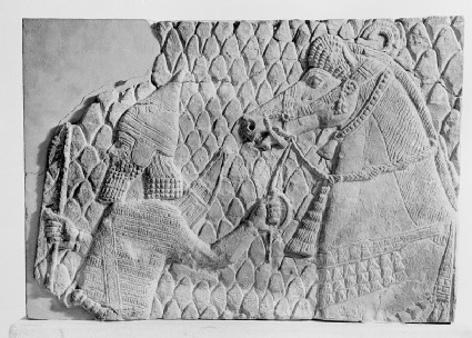 Relief, fragment depicting an Assyrian soldier holding a bow and leading a horse