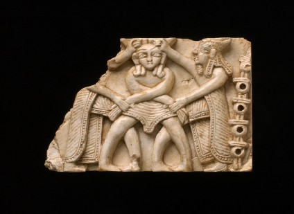 Ivory plaque, central figure has feathered headress, assailants are bewigged and crowned in Phoenician style