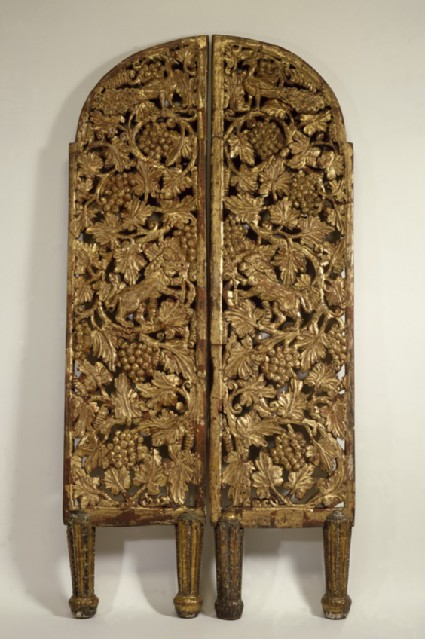 A pair of gilded wooden altar doors, decorated with vine scrolls inhabited by lions and peacocks