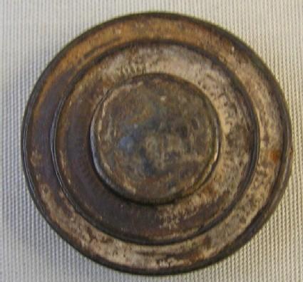 Bronze fibula, circular flat central boss, dark enamel, double spring coil