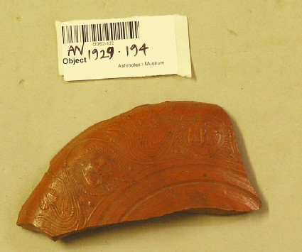 Fragment of red glaze bowl with a scroll design