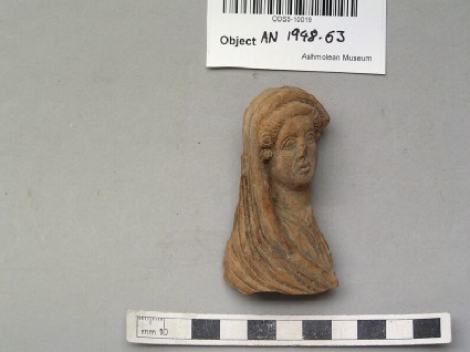 Head of female figurine with veil covering hair, back and shoulders
