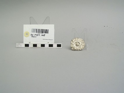 Silver disk ornament embossed with sun-design