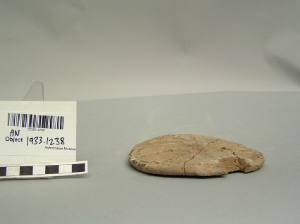 Disc with pattern made from small incised circles, a groove across it and fragment missing