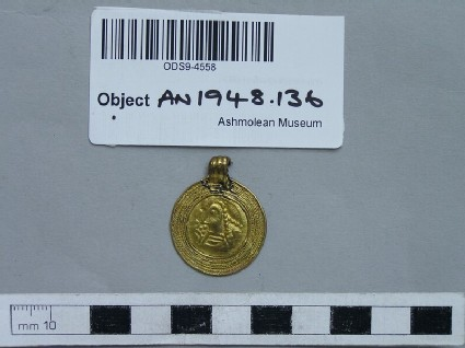 Gold coin pendant, within a circular frame decorated in filigree is set a Merovingian tremissis