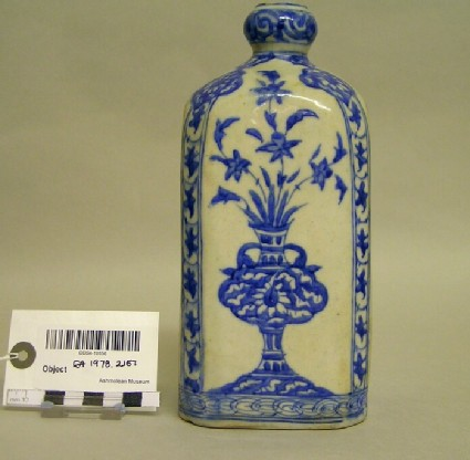 Bottle with vase of flowers