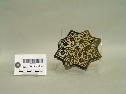Fragmentary star-shaped tile with floral sprays