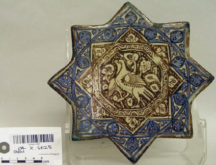 Star-shaped tile with bird against foliage