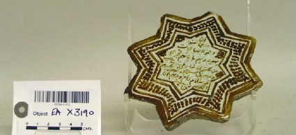 Star-shaped tile with inscription