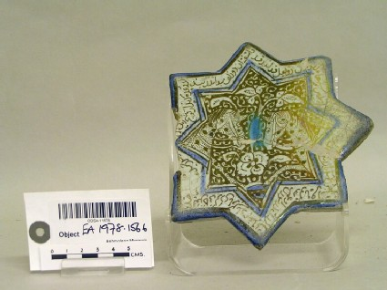 Star-shaped tile with two horse heads and inscription