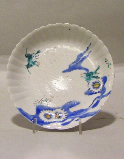 Fluted saucer with flying bird above water and plants