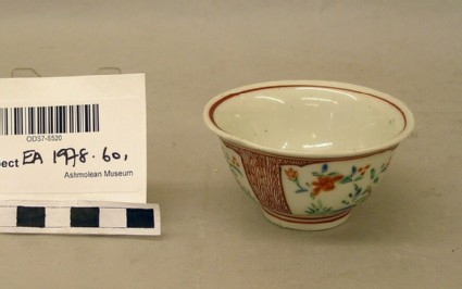 Cup with encircling red lines and three panels containing peonies