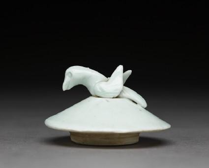 Lidded white ware jar surmounted by bird