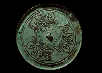 Ritual mirror with interlaced dragons on a geometric ground
