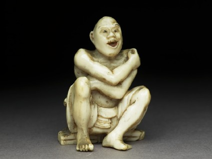 Netsuke in the form of man sitting on a mat made of twigs washing himself. He has a ladle in his left hand