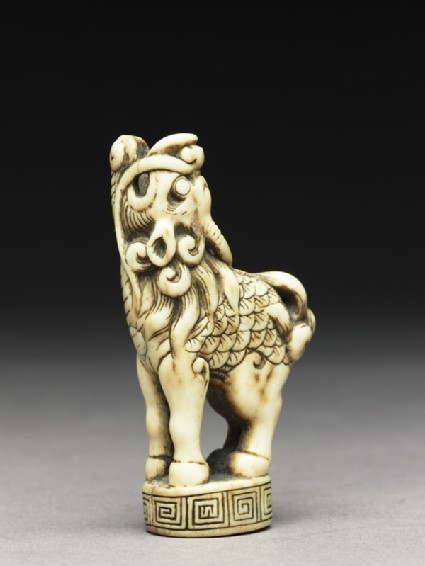 Netsuke in the form of a kirin standing on a small decorated base