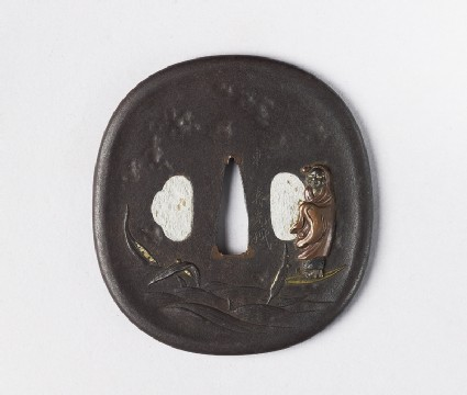 Round tsuba with design of Daruma floating on a bamboo leaf