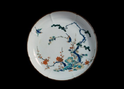 Lobed plate with pine, prunus, and bamboo growing from rocks