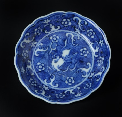 Blue-and-white dish with horse amid waves, and Prunus blossoms