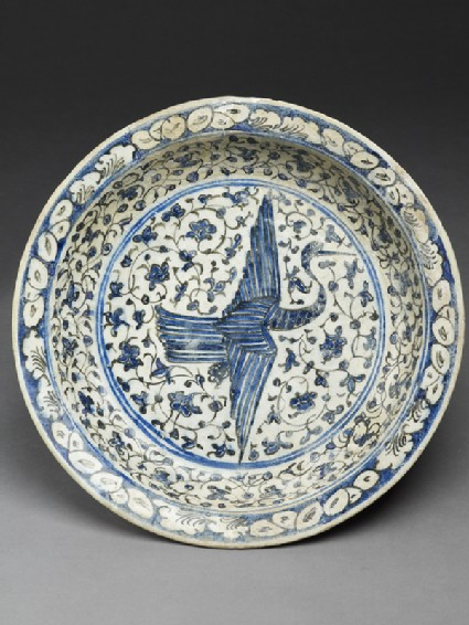Dish with flying crane against a floral background