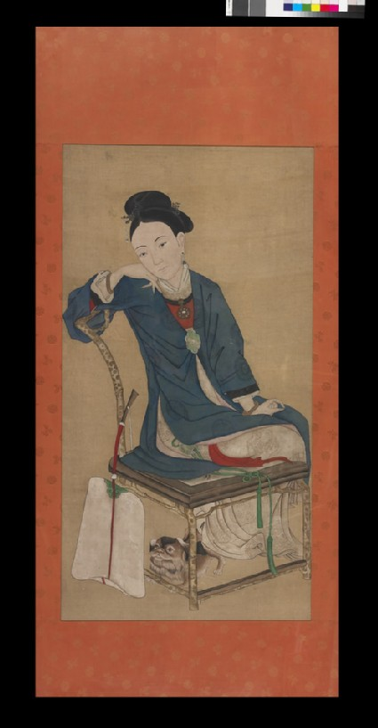 Girl seated with a fan and small dog