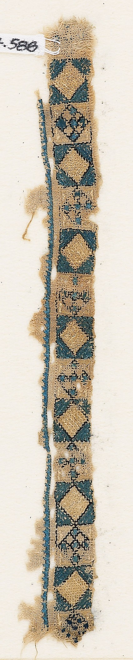 Textile fragment with band of diamond-shapes and crosses
