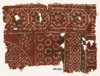 Textile fragment with rosettes in dotted frames, linked diamond-shapes, and Arabic inscription