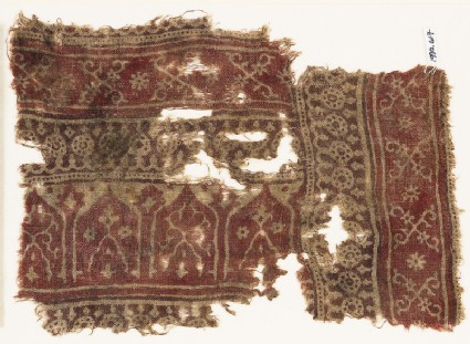 Textile fragment with bands of dotted circles, crossed tendrils, and arches