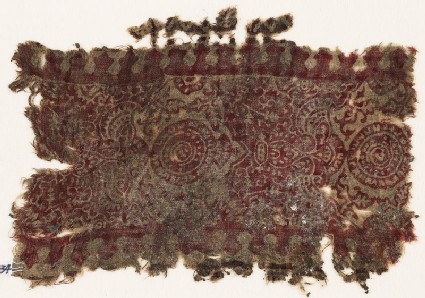 Textile fragment with ornate plants, leaves, and circles