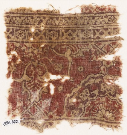 Textile fragment with ornate floral design and a large half-medallion