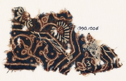 Textile fragment with curving tendril, leaves, and a flower
