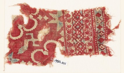 Textile fragment with stars, swastika, and possibly rosettes
