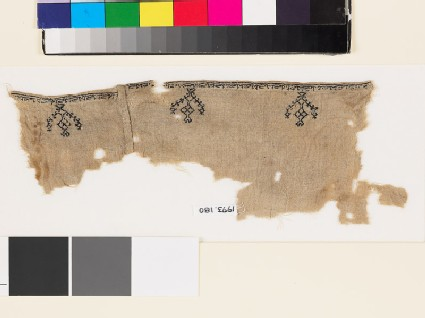Textile fragment from a garment with stylized birds, trees, and pseudo-kufic inscription