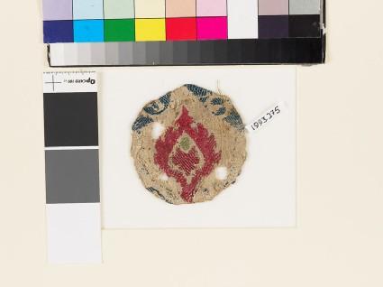 Roundel textile fragment with stylized leaf