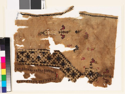 Textile fragment from the neck of a tunic with a V-shape, birds, and plants