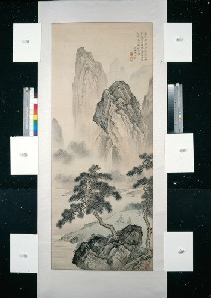 View of mountains with figures seated by a river