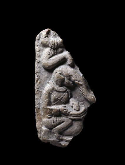 Fragment of a plaque with an elephant-headed figure playing a drum