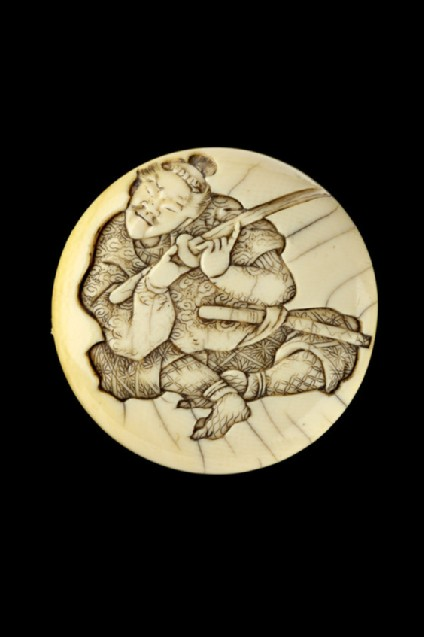 Manjū netsuke depicting a samurai testing the sharpness of his sword blade