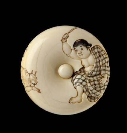 Manjū netsuke depicting a boy chasing away two oni, or demons