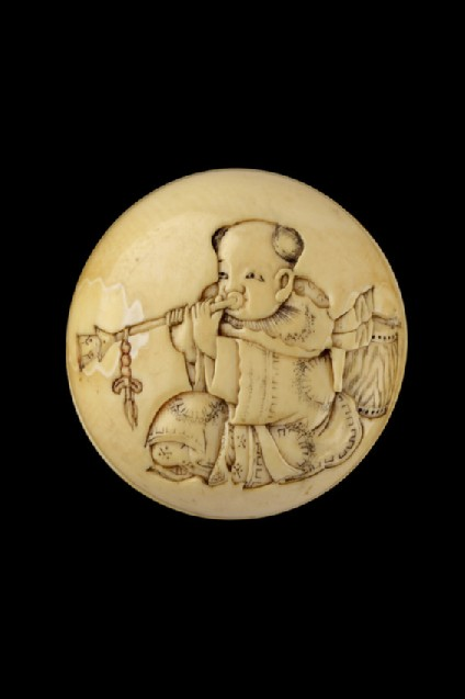 Manjū netsuke depicting a karako blowing a trumpet. Reverse, two masks and two drumsticks